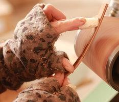 Het handmatig schuren van de pootjes van de houten zonnebril.