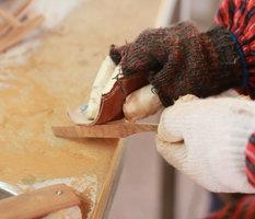 Het handmatig schuren met schuurpapier van de pootjes van de houten zonnebril