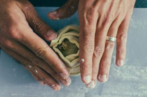 close up on hands wrapping fresh puff pastry around a pear - The Mummy
