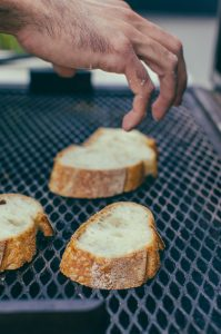 hand reaching for bread toasting on grill - The Mummy