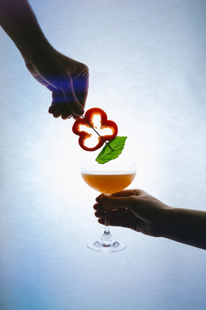 For our menu pairing with Image of silhouetted hand holding an orange cocktail for our menu pairing with Punch-Drunk Love we made a bell pepper cocktail being held by another hand