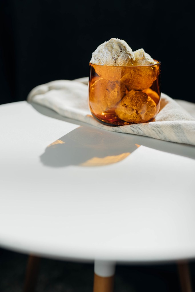 A collection of four Butterball Cookies sit in a clear amber glass that sits on a washcloth on top of a round white coffee table. The cup of Butterballs is set against a black backdrop.