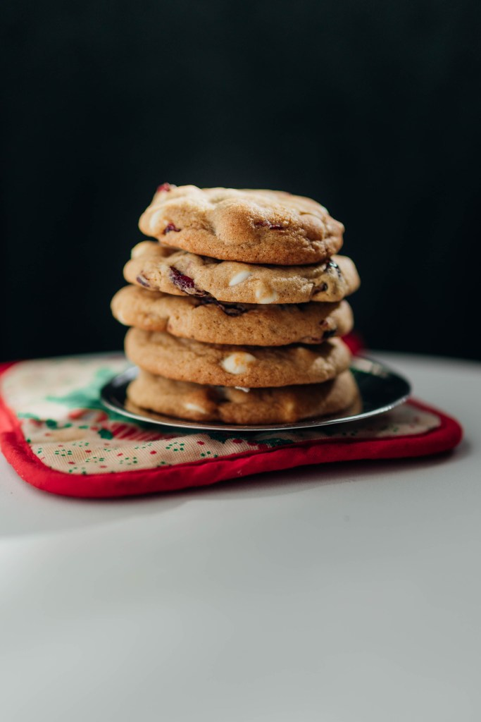 Straight-on view of a stack of five White Chocolate and Cranberry cookies we made for our Home Alone post. The cookies are stacked on a small silver platter seated on a holiday-themed pad.