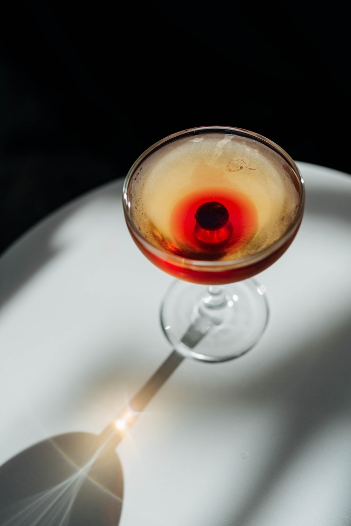 More top down view of the Thumbprint Cookie Cocktail we made for our Home Alone post. In this photo you can clearly see the brandied cherry and its juices around it creating a nice circle in the center of the couple glass. The Couple glass is casting a long shadow on a white round table.