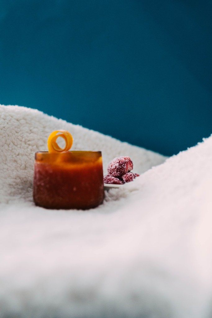 In the center of the frame is a pile of frozen strawberries. Out of focus to the left of it is an amber cocktail glass with a twisted orange peel on top. This set was put together to shoot our Snowpiercer menu.