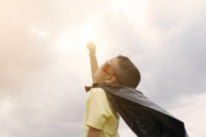 a kid dressed as superhero looking up the sky