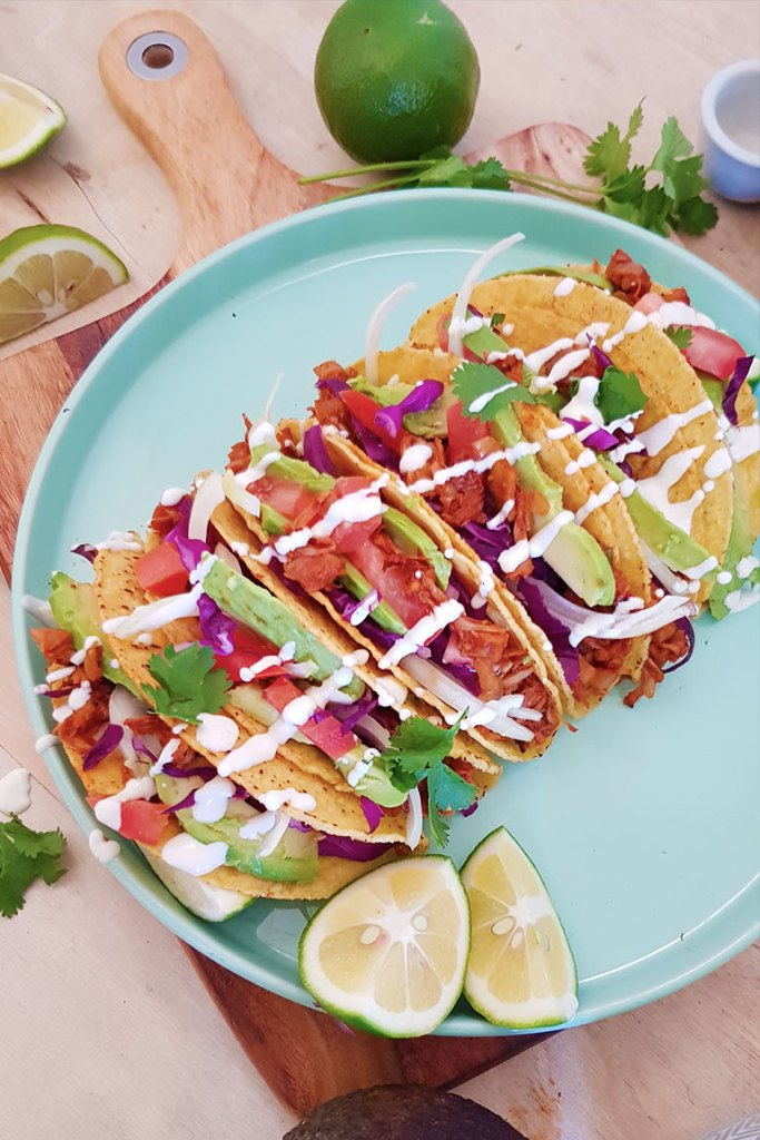 Tacos in a plate and slics of lime.