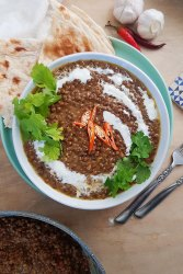 Lentil Curry in white bowl served with garlic naan