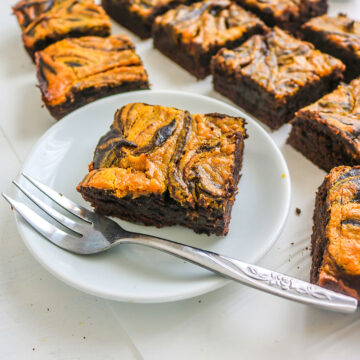 vegan pumpkin brownies on a white plate and a silver fork