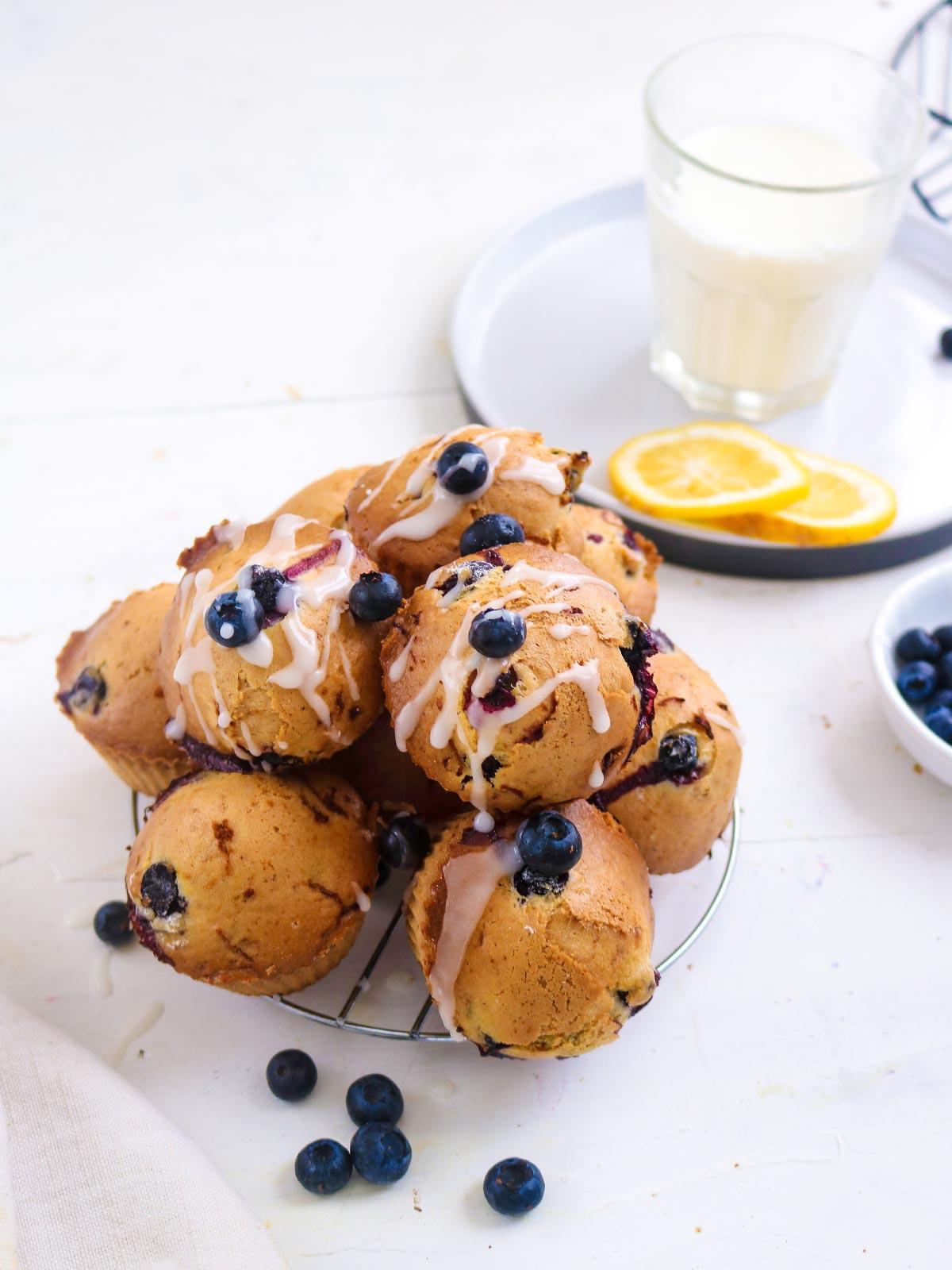 Vegan blueberry-lemon muffins with a sugar-lemon glaze. stack on a wire rack.