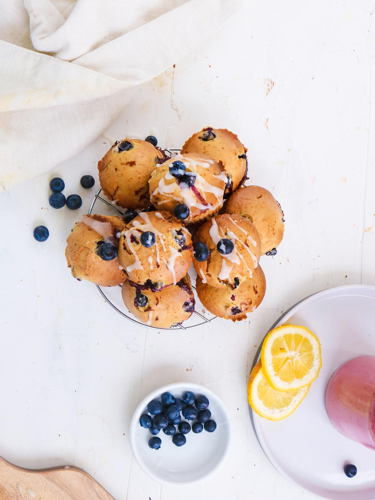 Vegan blueberry-lemon muffins with a sugar-lemon glaze. Stack on a wire carrier top view