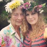 Grandmother and Granddaughter wearing Spring flowers in their hair; gardening