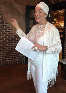 Nancy Wyatt dressed in white giving a speech at networking meeting