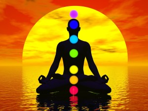 Silhouetted person in lotus pose with chakras shown