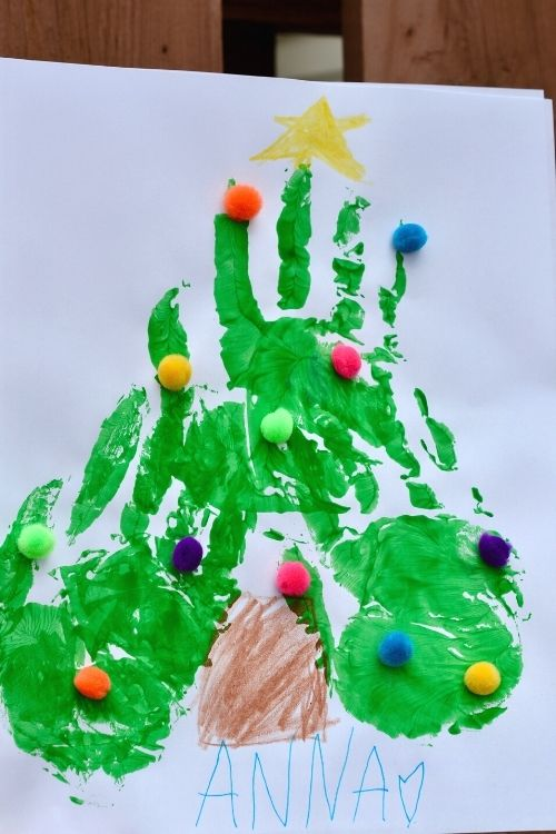 Christmas tree with fingerprints that includes three handprints and pom poms for decoration.