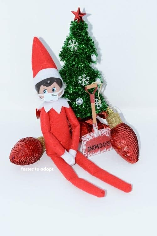 Elf sitting by Christmas tree and ornaments wearing a mask.