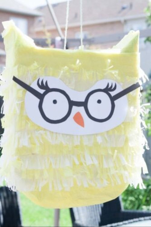 Owl pinata that is yellow and wears glasses.