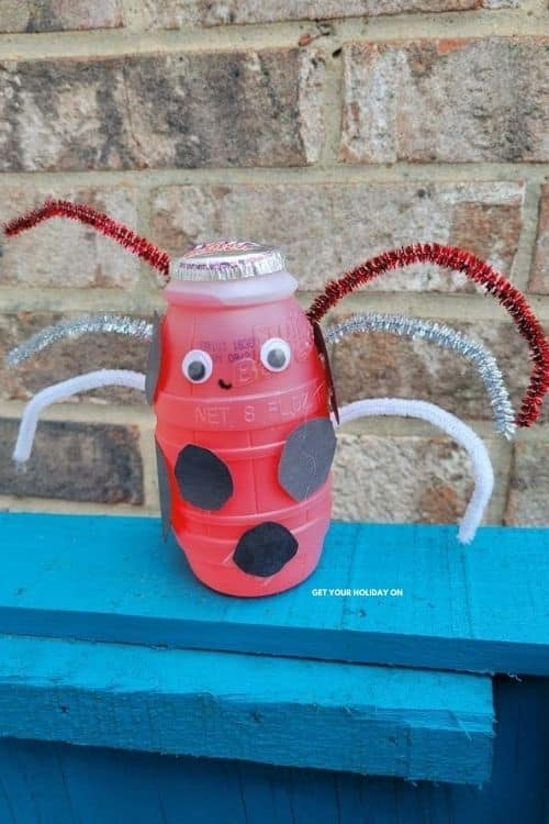 Ladybug craft with pipe cleaners, googly eyes, black construction paper and smile.