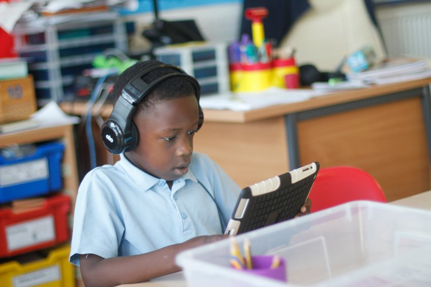 Young boy in a lesson using an iPad with earphones on