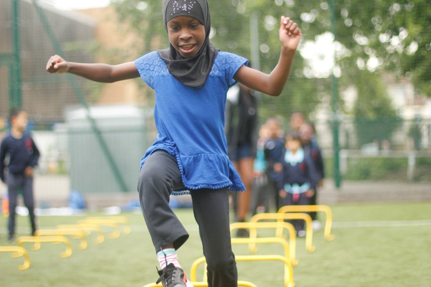 Girl jumping hurdles in PE