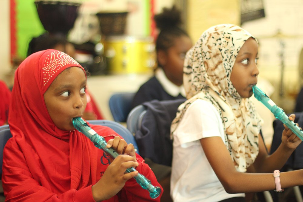Two girls focused on their recorder lesson