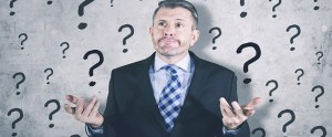 Confused businessman standing with question mark