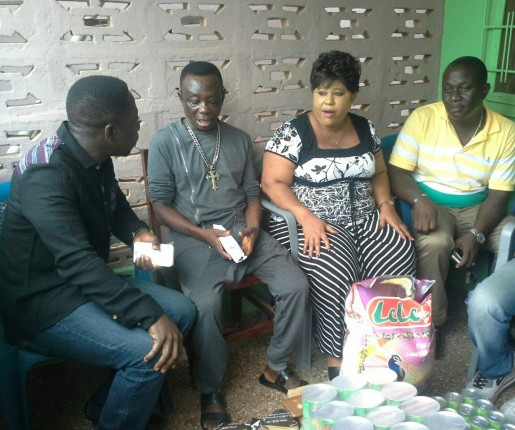 L-R: Mr Beatiful, presenting the items to J.A Adofo and his wife and other