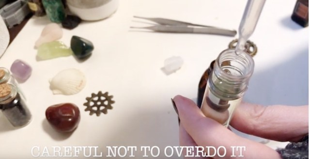 a hand holding a roller top bottle and adding oil to it