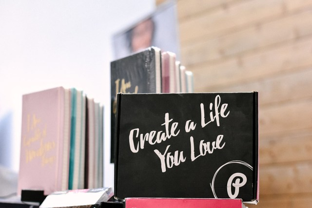 a card in a city window reading create a life you love.
