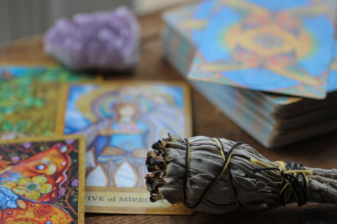 a deck of tarot cards, a crystal, and a smudge stick