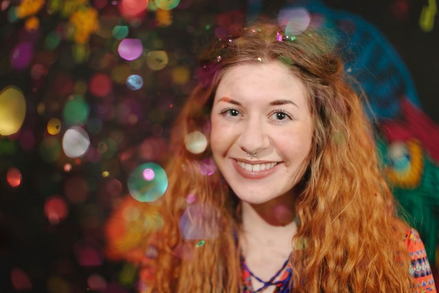 a woman with red hair and bright rainbow bokeh circles