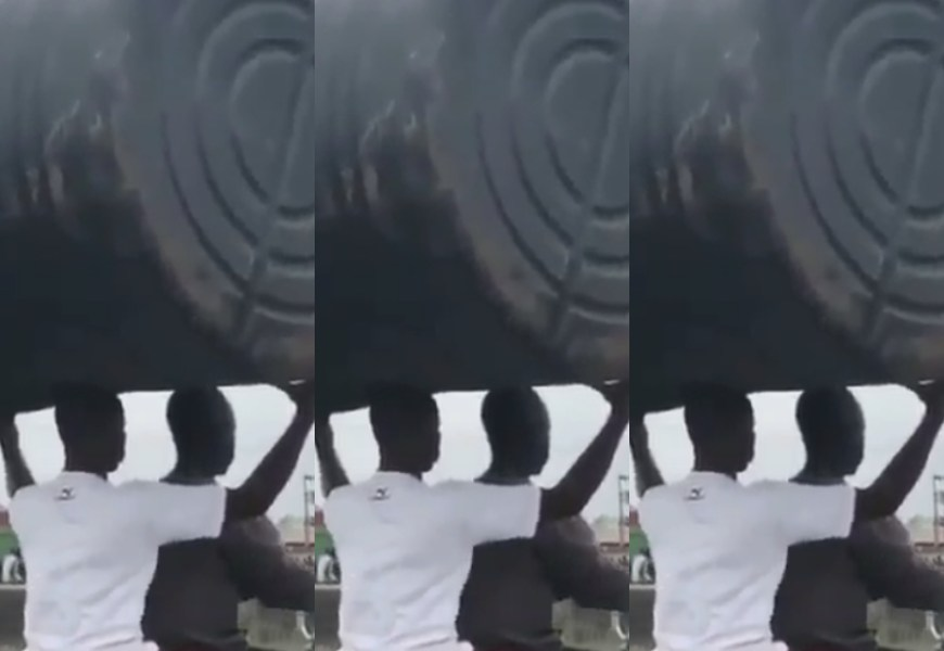 VIDEO: Young Guy Defies Odds As He Carried A Huge Water Tank On His Head While Sitting On A Moving Motorbike