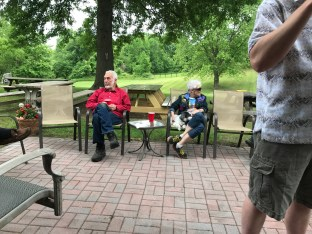 Sam, Gail, and Bandit (next to Gail) hang out at the party.