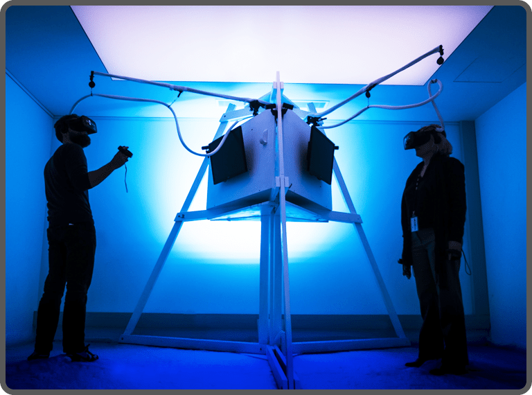 Two gamers playing VR game in a room with blue light