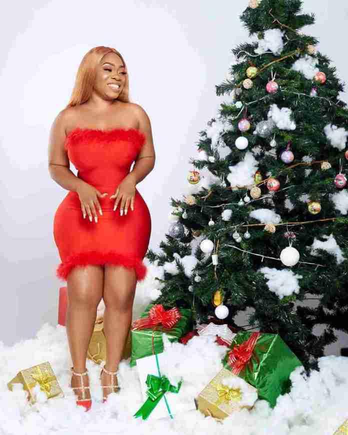 Actress Moesha posing with a Christmas tree