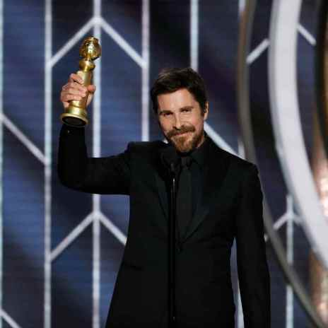 Christian Bale holding his Golden globes award