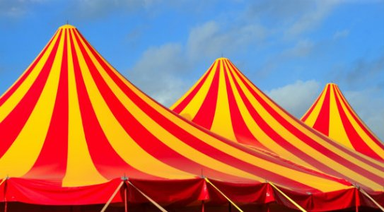 Circus tent red orange and yellow stripped pattern blue sky