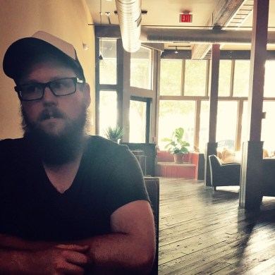 Photo of GigSalad employee and bassist for indie band posing in a coffee shop.
