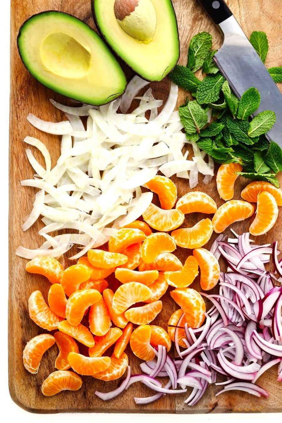 Cutting board with fresh avocado, fennel, red onion, mint and clementine oranges