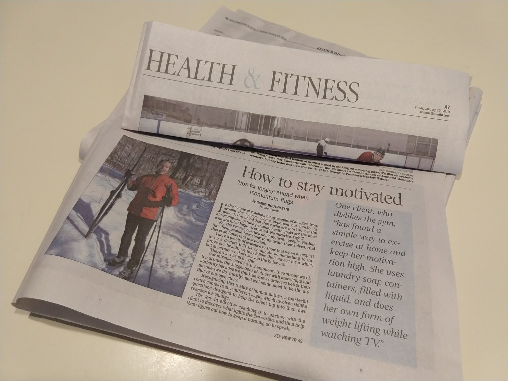 "Newspaper masthead reads Health & Fitness, folded to show article titled ""How to stay motivate"". Newspaper photo shows a person holding skis standing outside in the snow."