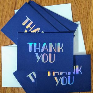 Close up of a pile of notecards. They are navy blue with silver block letters which read Thank you.