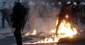 A riot policeman is set ablaze by a petr