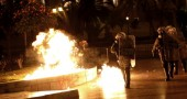 Riot policemen walk by as a petrol bomb,