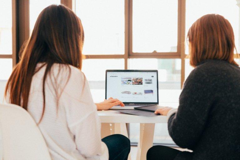 due donne che parlano mentre guardano il computer portatile