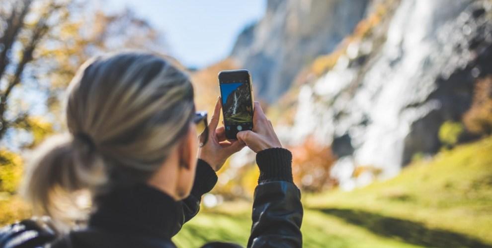 Woman Taking Photo of Waterfall