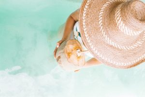 Woman with a straw hat standing in the water holding coconut water. Photo taken from above. Everyday Colorism in the Caribbean.