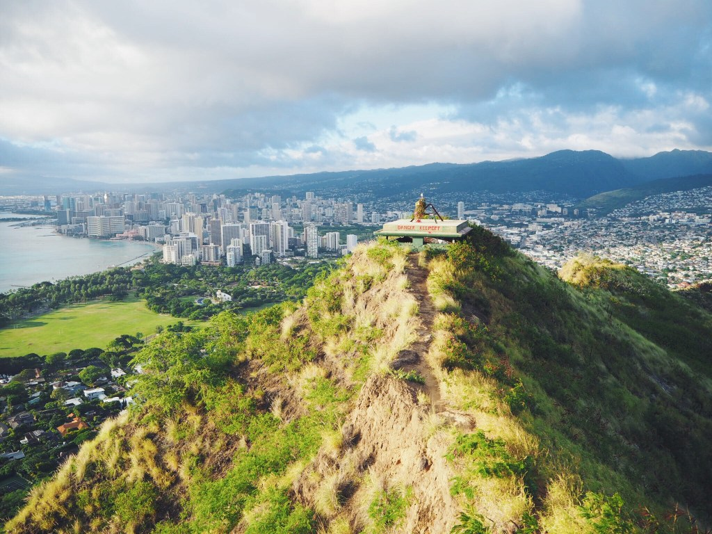 green rolling hills and view of Hawaiian city scape