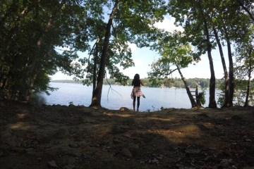 girl facing water standing on riverbank