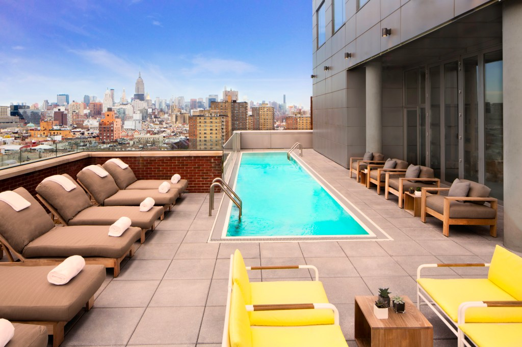 plunge pool on rooftop with luxurious deck chairs