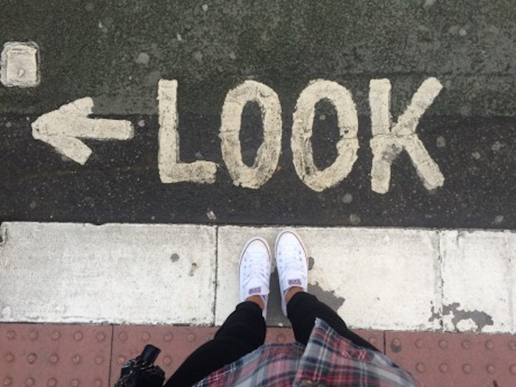 view of girls feet at road edge, look left sign on floor